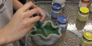 A child's hands brush glaze onto a wavy clay cup.