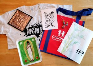 A collection of art projects, a CHOA tote bag, and a MCMA camp shirt