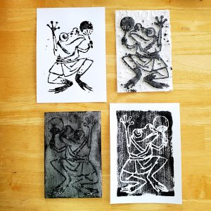 Two different block prints of a frog in a yukata dancing with a fan